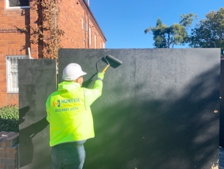 Jonas enjoying the weather while painting the site hoardings on a residential knock down rebuild in Randwick #painting #hlhgroup #hunterlabourhire #labourhiresydney #construction